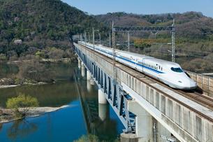 山陽新幹線N700と桜の高梁川の写真素材 [FYI03178410]