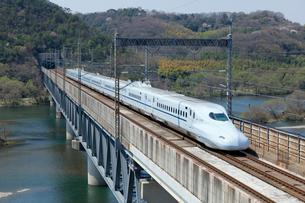 九州山陽新幹線と桜の高梁川の写真素材 [FYI03178412]