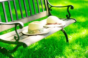 ベンチに置かれた男女の麦わら帽子の写真素材 [FYI03182347]