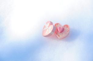 雪の上のハート形のプレゼントケースとハート形のクッキーの写真素材 [FYI03182423]