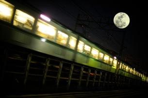 通勤電車と満月の写真素材 [FYI03182518]