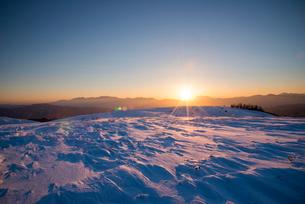 霧ヶ峰高原夕日に染まる雪原よりのぞむ中央アルプス乗鞍岳と夕日の写真素材 [FYI03184158]