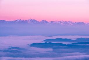 高ボッチ高原より朝焼けに染まる北アルプス連峰と松本の街並みを包む雲海の写真素材 [FYI03184700]
