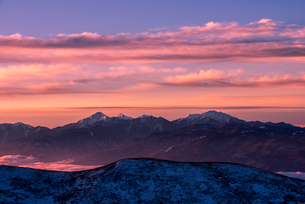 霧ヶ峰高原より朝焼けに染まる空と南アルプス連峰を望むの写真素材 [FYI03185143]