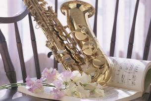 楽譜の上に置かれたサックスとスイートピーの写真素材 [FYI03186173]