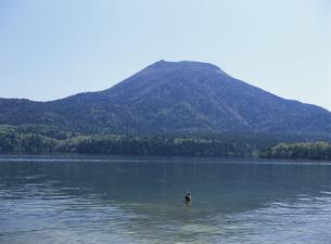 湖から見える山と釣りをする男性の写真素材 [FYI03188247]