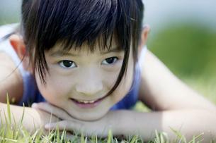 野原に伏せる日本人の女の子の写真素材 [FYI03190469]