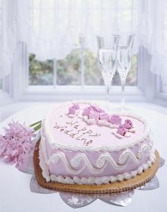 ウェディングケーキと花と2個のワイングラス(ピンク)の写真素材 [FYI03191721]
