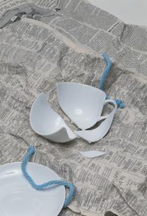 新聞紙の上の割れたカップの写真素材 [FYI03194453]