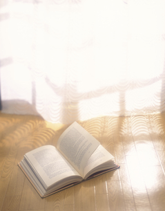 窓辺のフローリングに置かれた本の写真素材 [FYI03197200]