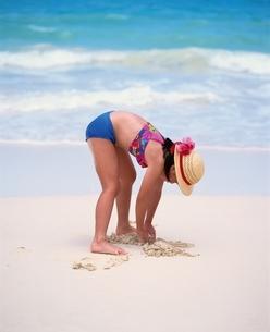 海辺で砂遊びをする帽子とビキニの日本人の女の子の写真素材 [FYI03198344]