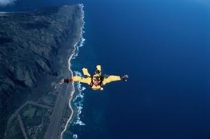 スカイダイビングする人と海岸線の空撮 ハワイ アメリカの写真素材 [FYI03199738]