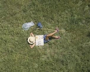草原で昼寝をする日本の子供の写真素材 [FYI03200322]