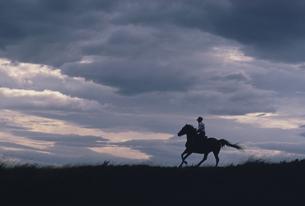 野原で乗馬する人物と彩雲の写真素材 [FYI03201113]