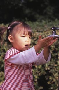 蛇口に手を差し出す日本人の女の子の写真素材 [FYI03204098]
