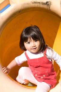 トンネルの滑り台で遊ぶ女の子の写真素材 [FYI03204213]