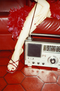 赤いソファに座る女性の手足とラジオの写真素材 [FYI03204618]