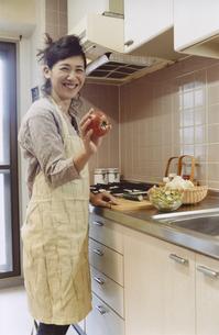 キッチンで調理するエプロン姿の日本人女性の写真素材 [FYI03204624]