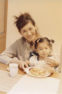 女の子を膝に乗せてホットケーキを食べさせる母親 日本人の写真素材 [FYI03204634]