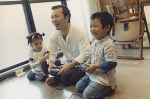 床に座りゲームをする父親と男の子と女の子 日本人の写真素材 [FYI03204642]