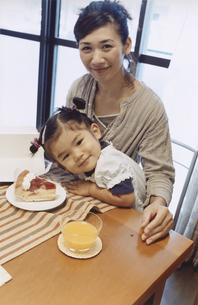 女の子を膝に乗せてショートケーキを食べさせる母親 日本人の写真素材 [FYI03204647]