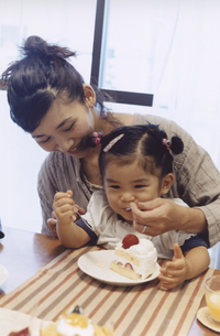 女の子を膝に乗せてショートケーキを食べさせる母親 日本人の写真素材 [FYI03204648]