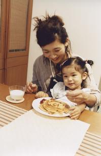 女の子を膝に乗せてホットケーキを食べさせる母親 日本人の写真素材 [FYI03204649]