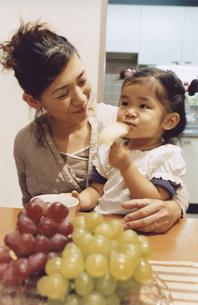 母親の膝に乗りリンゴを食べる女の子 日本人の写真素材 [FYI03204652]