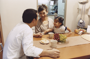 食卓で母親の膝に乗り父親と睨めっこする女の子 日本人の写真素材 [FYI03204657]