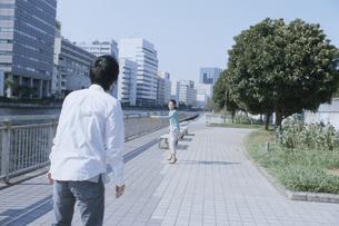 運河脇の公園でフリスビーをする日本人カップルの写真素材 [FYI03204663]