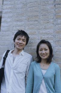 レンガの壁に寄り掛かる日本人カップルの写真素材 [FYI03204666]