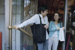店頭のドアを開ける日本人カップルの写真素材 [FYI03204669]