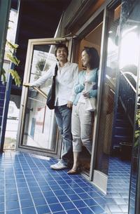 店頭のドアを開ける日本人カップルの写真素材 [FYI03204670]
