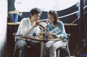 カフェでCDを見る日本人カップルの写真素材 [FYI03204674]