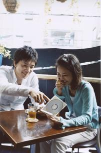 お茶を飲みながらCDを見る日本人カップルの写真素材 [FYI03204676]