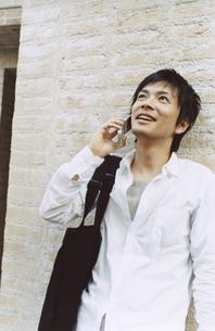 レンガの壁に寄り掛かり携帯電話で話す日本人男性の写真素材 [FYI03204678]