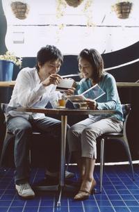 お茶を飲みながらCDを見る日本人カップルの写真素材 [FYI03204679]