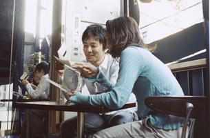 お茶を飲みながらCDを見る日本人カップルの写真素材 [FYI03204681]