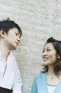 レンガの壁の前で見つめ合う日本人カップルの写真素材 [FYI03204682]