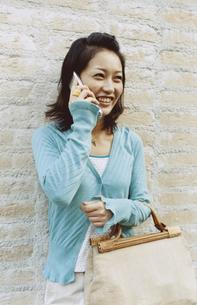 レンガの壁に寄り掛かり携帯電話で話す日本人女性の写真素材 [FYI03204683]