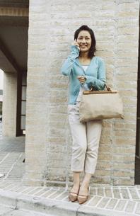 レンガの壁に寄り掛かり携帯電話で話す日本人女性の写真素材 [FYI03204686]