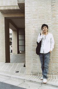 レンガの壁に寄り掛かり携帯電話で話す日本人男性の写真素材 [FYI03204688]