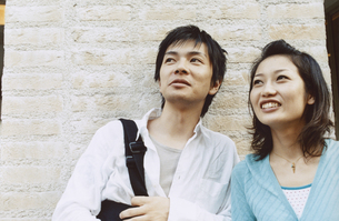 レンガの壁の前の日本人カップルの写真素材 [FYI03204689]