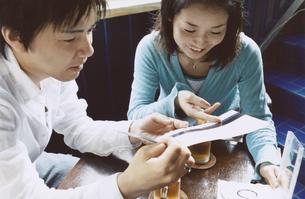 お茶を飲みながらCDを見る日本人カップルの写真素材 [FYI03204693]