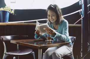 お茶を飲みながらCDを見る日本人女性の写真素材 [FYI03204700]