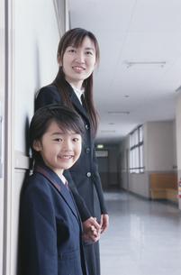 学校の廊下で手をつなぐ日本人の小学生と女性の写真素材 [FYI03205211]