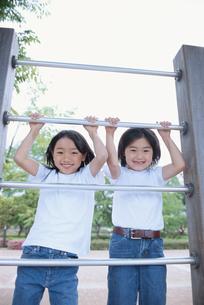 鉄棒をする女の子と男の子の写真素材 [FYI03205334]