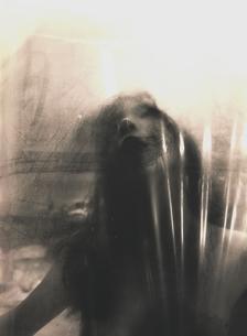 ビニールに顔を押しつける日本人女性 セピアの写真素材 [FYI03206524]