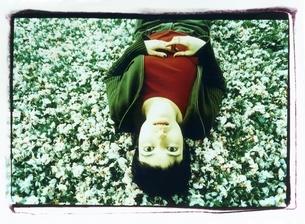 桜の花びらに寝転がる外国人女性の写真素材 [FYI03207223]