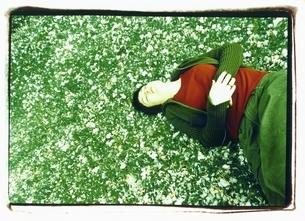 桜の花びらに寝転がる外国人女性の写真素材 [FYI03207225]
